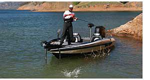 Bass Boat With Angler Catching A Fish