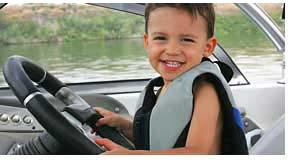 Young Boy Driving A Boat